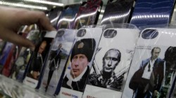 Mobile phones cases displaying images of Russian President Vladimir Putin, are pictured on display at an electronic store in Stavropol