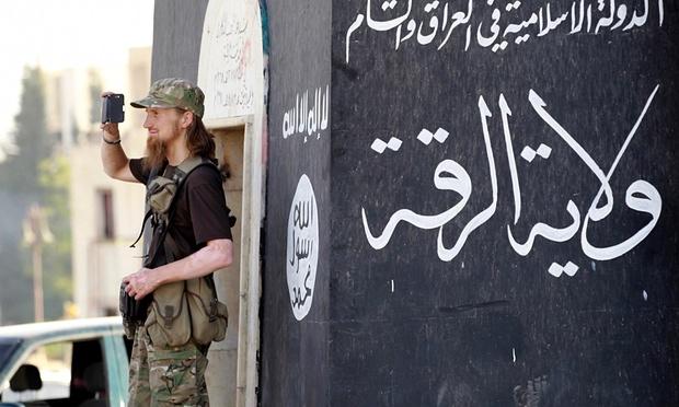 Militantný islamský bojovník filmuje vojenskú prehliadku v severnej Sýrii na oslavu vyhlásenia islamského kalifátu. Foto: Reuters