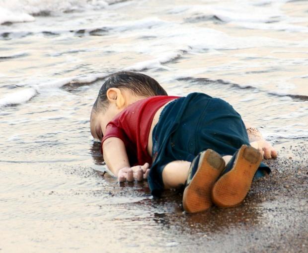 Podľa svedectva jedného z príbuzných pochádzal trojročný Ajlan Kurdí z rodiny sýrskych migrantov, ktorá utiekla z vojnou zničeného mesta Kobané a pokúšala sa dostať do Kanady. Bezvládne telo malého Ajlana vyplavilo v stredu na pláž pri letovisku Bodrum, ktoré leží na pobreží Egejského mora na juhozápade Turecka.  Foto: Nilufer Demir / Reuters